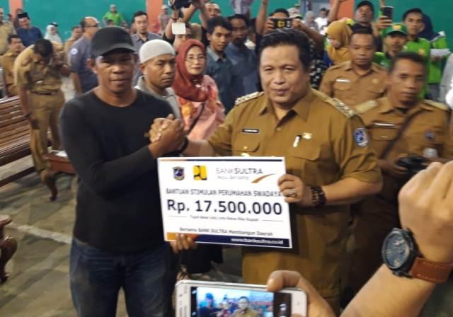 Ketgam : Bupati Muna Rusman Emba saat menyerahkan secara simbolis tabungan rekening bantuan rumah BSPS kepada warga/foto: Rasyd Suyoto