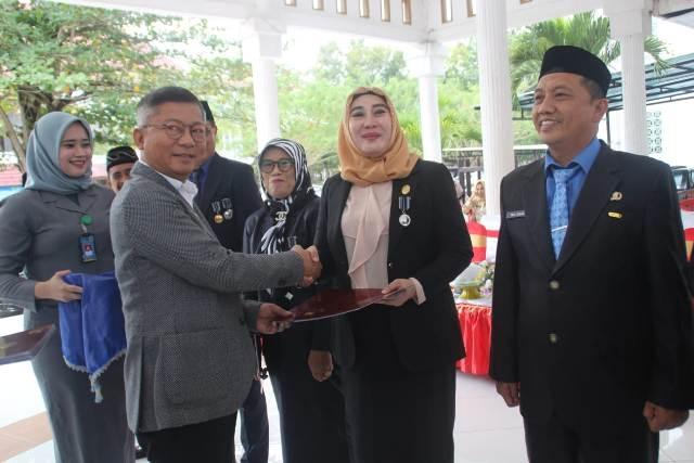 Ketgam : Wakil Bupati Konawe Gusli Topan Sabara saat menyerahkan secara simbolis sertfikat Satya Lancana Karya Satya pada salah seorang ASN Konawe
