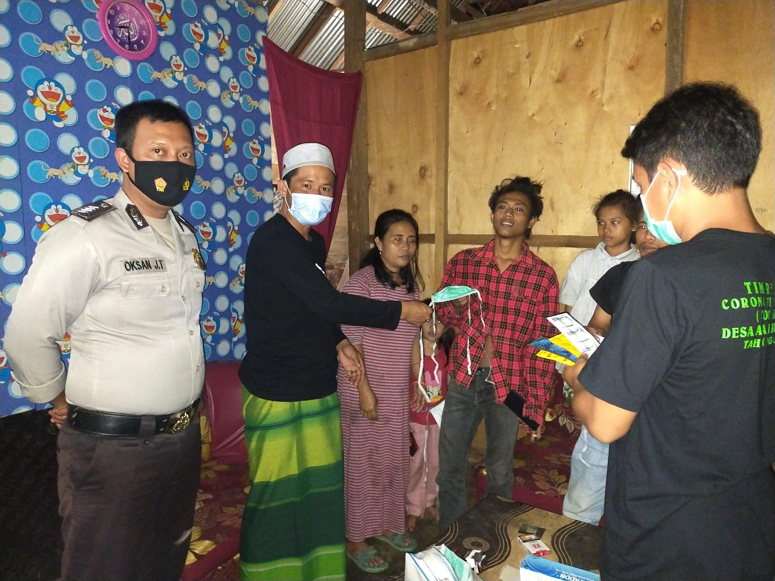 Ketgam : Kepala Desa Asaki Samsul Jaiz saat menyerahkan masker yang di dampingi Bhabinkamtibmas Oksan JT serta tim relawan covid-19.